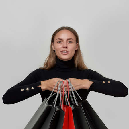 Content young caucasian woman wearing black clothes smiling and showing shopping bags for camera, posing isolated over light background 免版税图像