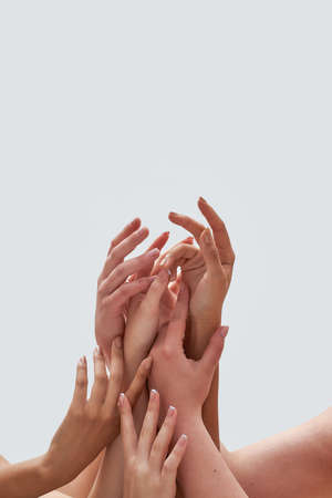 Close up of group of delicate female hands together isolated over white background 免版税图像