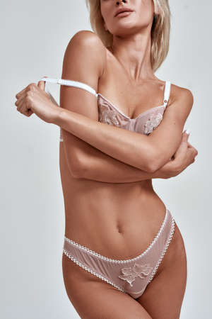 Cropped shot of young sensual woman with fit slim body wearing sexy lingerie adjusting strap on her bra while posing isolated over grey background 免版税图像