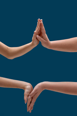 Close up of two women holding or measuring hands, touching each other palms isolated over blue background