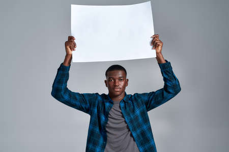 Serious young african american guy in casual clothes looking at camera, displaying blank banner ad, holding it above his head, posing isolated over gray background 免版税图像
