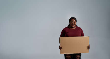 Joyful plus size young african american woman in casual clothes smiling at camera, holding blank cardboard banner ad in front of her, posing isolated over gray background