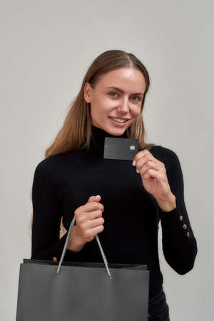 Smiling young woman wearing black clothes showing plastic credit card while posing with shopping bag isolated over gray background