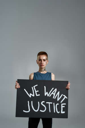 Confident tattooed young caucasian female activist looking at camera, holding cardboard banner with We want justice text, posing isolated over gray background 免版税图像