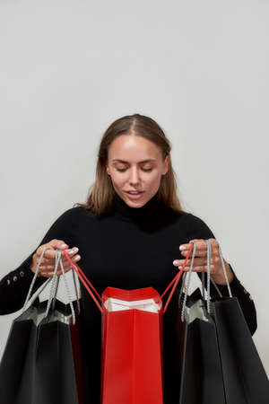 Portrait of curious young caucasian woman dressed in black looking inside one of many shopping bags while standing isolated over light gray background
