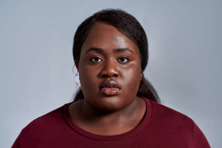 Close up portrait of serious plus size young african american woman in casual clothes looking at camera while posing isolated over gray background 免版税图像