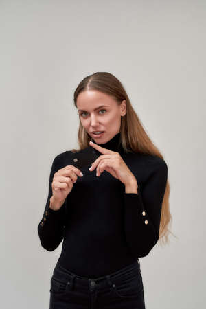 Beautiful young woman wearing black clothes looking at camera, holding plastic credit card while posing isolated over gray background