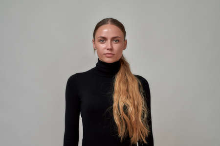 Portrait of beautiful caucasian female model with long hair wearing black turtleneck looking at camera, standing isolated over gray background