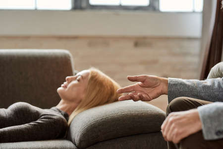 Psychoanalyst talking to young caucasian woman lying on sofa