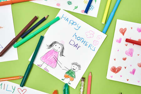 Happy mothers day. Colorful child drawings and felt tip pens lying on green table
