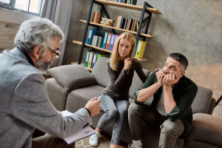 Psychotherapist talking to man during appointment in cabinet