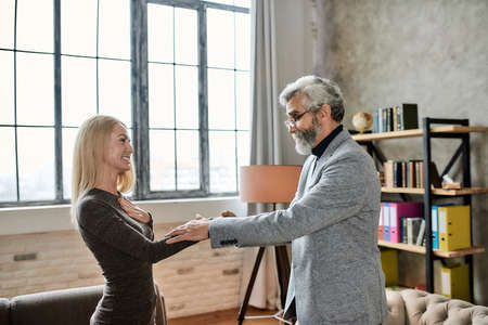 Happy young caucasian woman shaking hand of psychotherapist