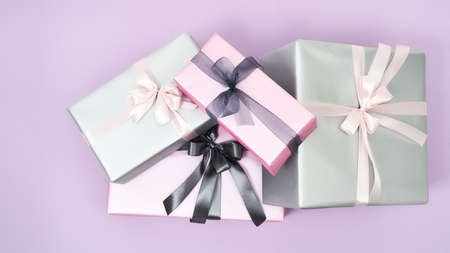 Happy Womens day. Top view of many colorful wrapped gift boxes with bows on a purple background