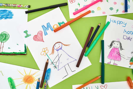 I love mom. Top view of colorful child drawings for mothers day and felt tip pens lying on green table