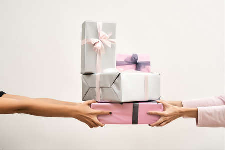 Choosing the best gift for a woman, mother, daughter. Female hands holding colorful gift boxes against light background