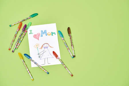 Handmade greeting card for the best mom in the world. Top view of colorful child drawing with colored pens or pencils for mothers day on a green background 免版税图像