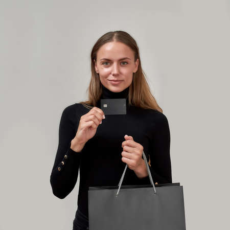 Stylish young woman wearing black clothes looking at camera, showing plastic credit card while posing with shopping bag isolated over gray background 免版税图像