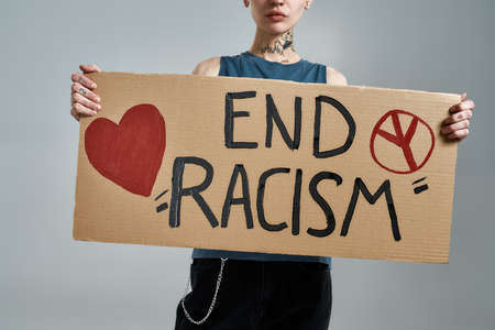 Cropped shot of tattooed young caucasian female activist looking at camera, holding cardboard banner with End Racism text, posing isolated over gray background