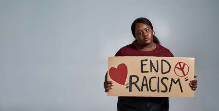 Tired plus size young african american woman in casual clothes looking at camera, holding End Racism banner in front of her, posing isolated over gray background 免版税图像