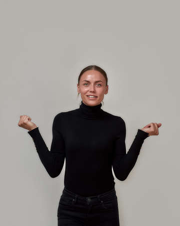 Delighted caucasian woman wearing black turtleneck smiling at camera, standing with raised hands presenting your product isolated over gray background