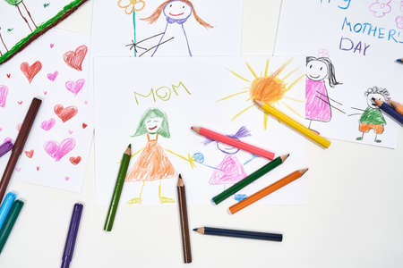 I love you, mom. Top view of beautiful colorful child drawings for mothers day and colored pencils on white background, handmade gift. 免版税图像