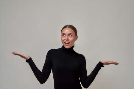 Portrait of surprised beautiful caucasian young woman wearing black turtleneck presenting your very exciting product, standing isolated over gray background 免版税图像