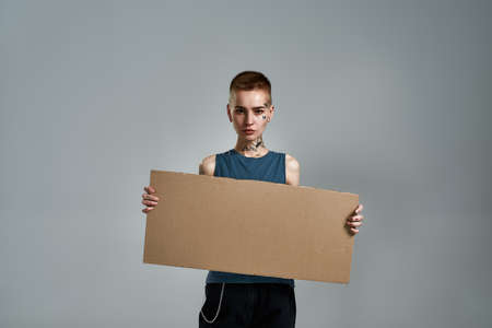 Tattooed young caucasian woman with piercing looking at camera, holding cardboard banner in front of her while posing isolated over gray background