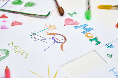 The best homemade gifts for Mom from kids. Top view of beautiful colorful child drawings for mothers day on white background