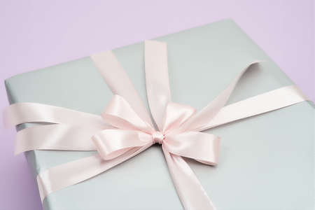 Gift for the special woman in your life. Top view of a gift box with pink bow on a purple background, copy space for text. Holidays and celebration concept