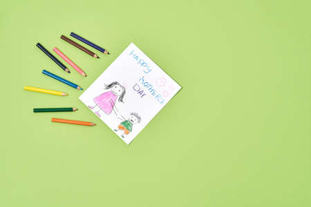 Unique gift for mom. Top view of a child drawing for Mothers day and colored pencils on a green background, copy space for text 免版税图像