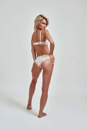 Full length shot of young sensual woman with perfect legs and wearing white lace lingerie looking playfully at camera, posing isolated over grey background