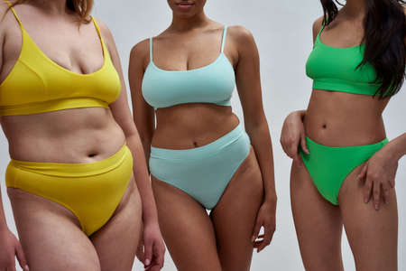 Cropped shot of diverse young women with different body shapes in colorful underwear posing together isolated over light background Foto de archivo