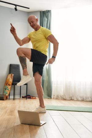 Sports man leading online workout at home 免版税图像