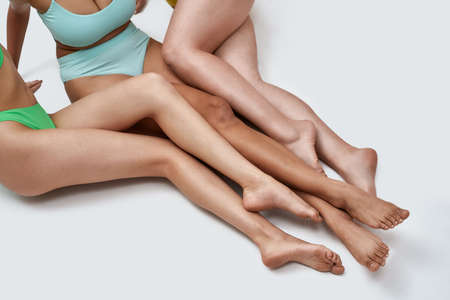 Close up shot of beautiful legs of three diverse young women in colorful underwear posing on the floor isolated over white background 免版税图像