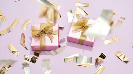 Happy womens day. Top view of two small wrapped gift boxes with golden bows on pastel pink background