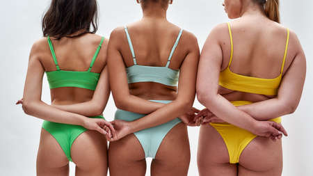 Cropped shot of three women with different body types in colorful underwear holding hands, supporting each other while posing isolated over white background Imagens