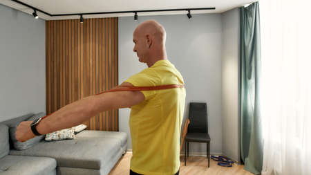 Bald man works out at home on self-isolation