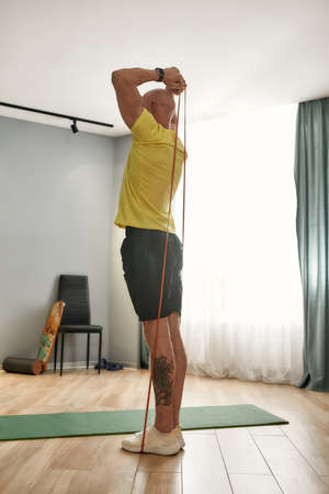 Athlete exercising at home with exercising band