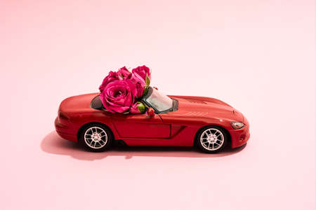 Red car with flowers standing on a pink background