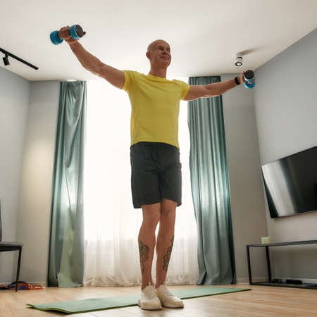 Man exercising at home near a sports mat 免版税图像