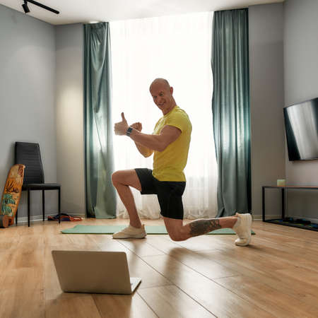 Trainer in sportswear training online at home