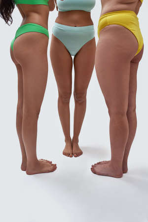 Close up of legs of three women with different body types posing in colorful underwear while standing over white background Imagens