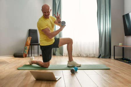 Trainer leading a workout with dumbbells