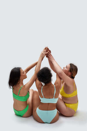 Back view of diverse women with different body types in colorful underwear putting hands up together to show support while sitting on the floor isolated over white background