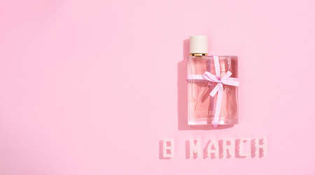 Present for beloved woman. Perfume bottle with bow and text 8 MARCH made with two little roses and white plastic letters over pink background