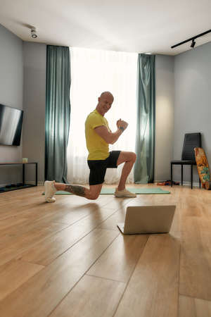 Man doing squatting while exercising at home