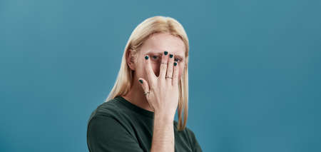 Young caucasian man looking through his manicured hand