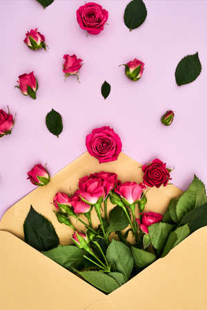 Beautiful envelope in roses lying on a pink