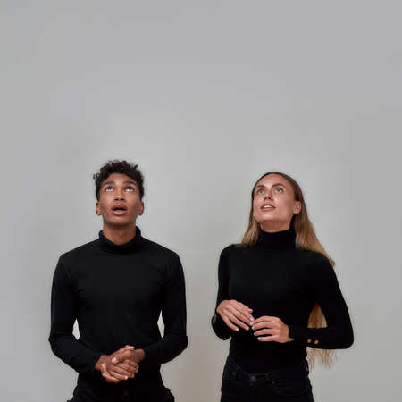 Stylish young woman and guy dressed elegantly in black looking up surprised at something while standing together isolated over gray background