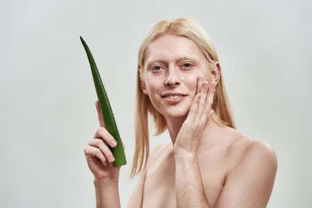Handsome young blond man holding fresh aloe leaf 免版税图像
